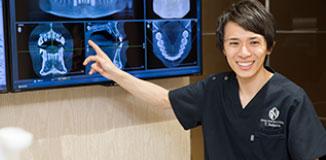 レントゲン写真を使って説明する歯科医師