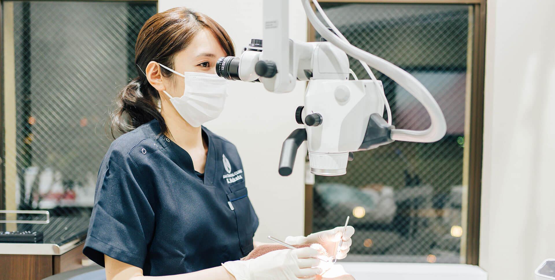 歯科用マイクロスコープを使用して診療する歯科医師